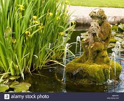 a moss covered statue of pan with pipes in an ornamental