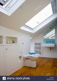 velux windows in modern white loft conversion bathroom with wooden