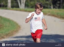 11 year boy running up road stock photo royalty free image