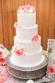 white wedding cake with coral flowers coral and gold flecked