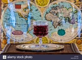 Ancient World Map by Wine Glass On Silver Platter On Wooden Table With Ancient World
