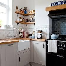 white kitchen corner with metro tiles and wooden worktop metro