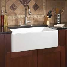 white sink black countertop white porcelain sink installed in the kitchen with wooden cabinets