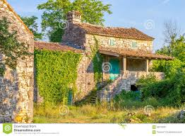 old stone mediterranean house ruins with ivy and grass stock photo