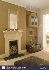 logs in cream fireplace in pale brown living room with old leather