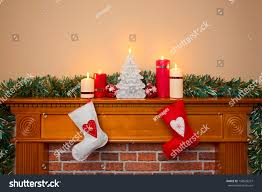 christmas stockings hanging over fireplace candles stock photo