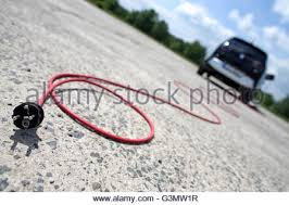 symbolic image a red electric cable behind a bmw i3 electric car