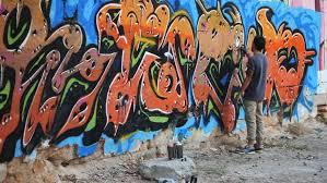 How To Graffiti With Spray Paint - graffiti artist paint spraying the wall urban outdoors street art
