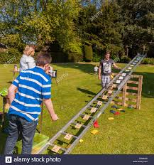 a boy playing the ladder and beanbag game at a village fete at