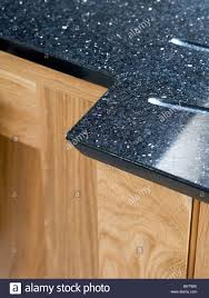 Worktop Close Up Of Black Granite Worktop On Pale Wood Kitchen Unit Stock