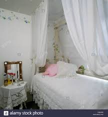 white voile drapes above single bed with white lace bedlinen in