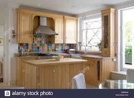 backsplash colourful tiles kitchen wooden units and island unit
