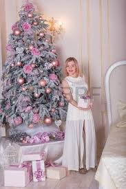 beautiful blonde in a white dress in christmas decorations stock