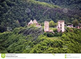 ruins of old castle in the middle of the forest hills stock photo