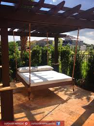 Pergola Mosquito Net by White Bedlinen And Pillows On Hanging Bed With Travertine Canopy
