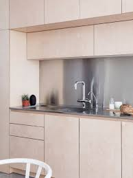 light wood cabinets with stainless steel countertops and kitchen ideas this contemporary kitchen has hardware free light plywood kitchen cabinetry and a