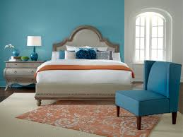 bright bedroom design with light blue accent wall color and orange