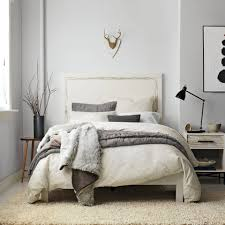 neutral colored bedding blue grey walls and pillows yellow beige carpet and bedding