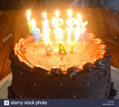 a chocolate birthday cake with lit candles stock photo royalty