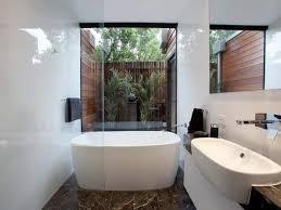 narrow bathroom with vessel sink and freestanding bathtub