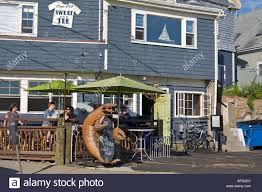 people sit outside a restaurant decorated with a large lobster