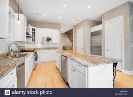 white kitchen cabinets wood floors a large white kitchen in a luxurious home with wood floors