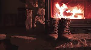 man hand takes warm winter boots from a shelf near fireplace 4k