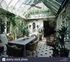 table and wicker chairs in large traditional conservatory dining