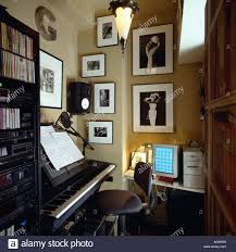 black white photographs on wall of small music room with electric