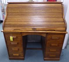 a pair of hummingbird chairs and an oak roll top desk
