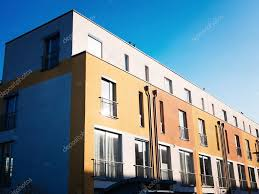 Modern Row Houses - modern row houses in yellow and orange with blue sky u2014 stock photo
