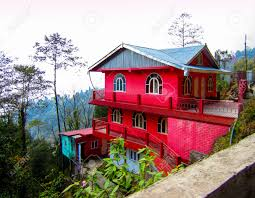 red house on a hill slope surrounded by trees and plants shot