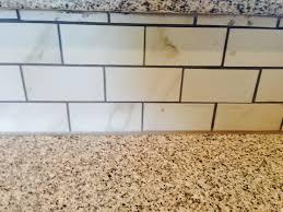 granite countertop with brick pattern ceramic tile backsplash