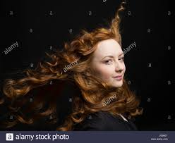 portrait confident woman with wind blowing long curly red hair