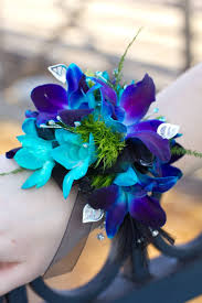 blue orchid corsage a spray of dendrobium orchids nestles against shiny green leaves