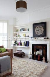 ornaments on shelving next to fireplace in white living room of