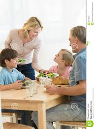 woman serving food to daughter at dining table stock photography