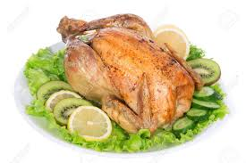 garnished roasted thanksgiving chicken on a plate decorated with