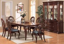 fancy oval wooden dining table with white uphostered chairs