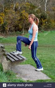 keep fit exercise woman step ups using a park bench stock photo