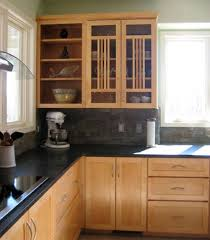 black counter tops and wood floors with the light cabinets is