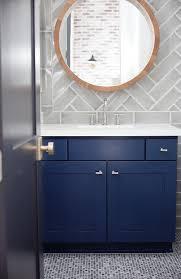 blue bath vanity with gray herringbone tile backsplash