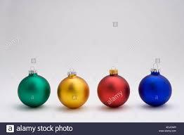 four tree bulb ornaments on white background studio