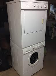 interior design dark hardwood floor with stackable washer dryer