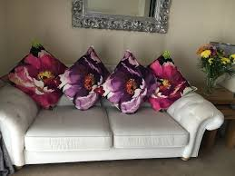cream sofa with matching purple accent chair and cushions in