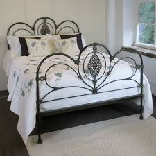bedroom black cast irod bed frame with headboard and wite bed