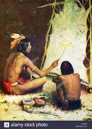 a native american artist is painting in sign language on buckskin