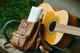 brown acoustic guitar beside brown leather bucket backpack on