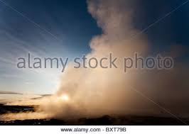 iceland geysir rising sun lights tower of boiling steam erupting