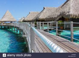 walkway leading to luxurious overwater bungalows with thatched